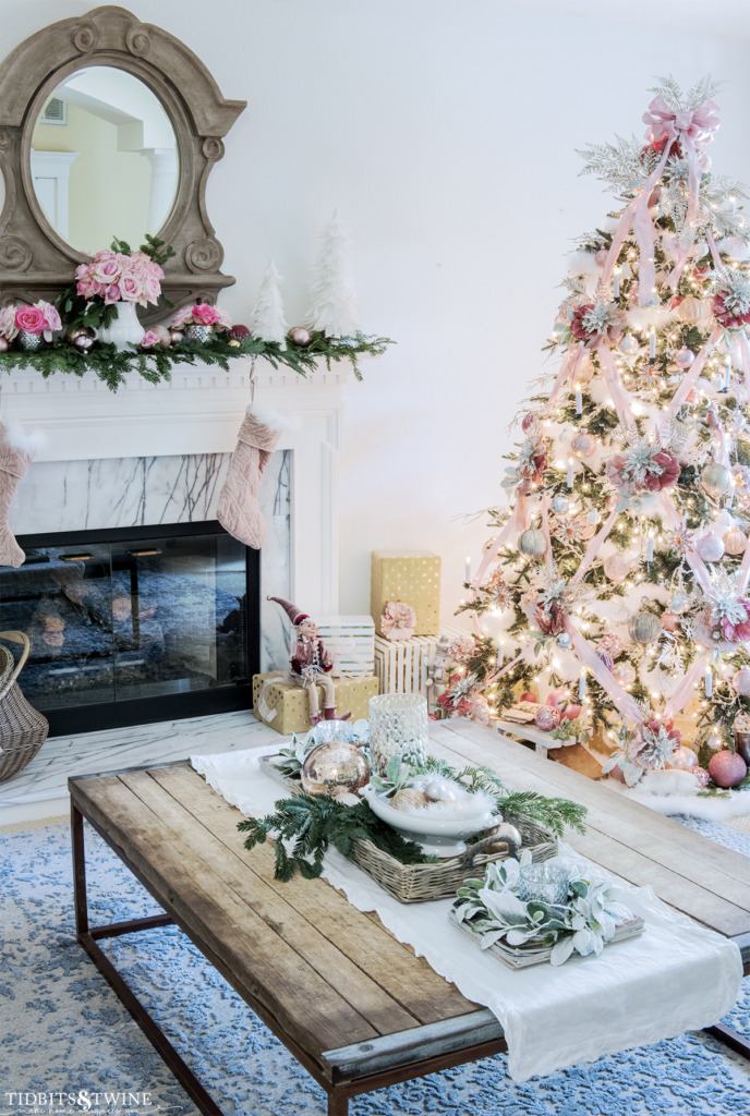Pink and white Christmas living room with decorated fireplace and tree