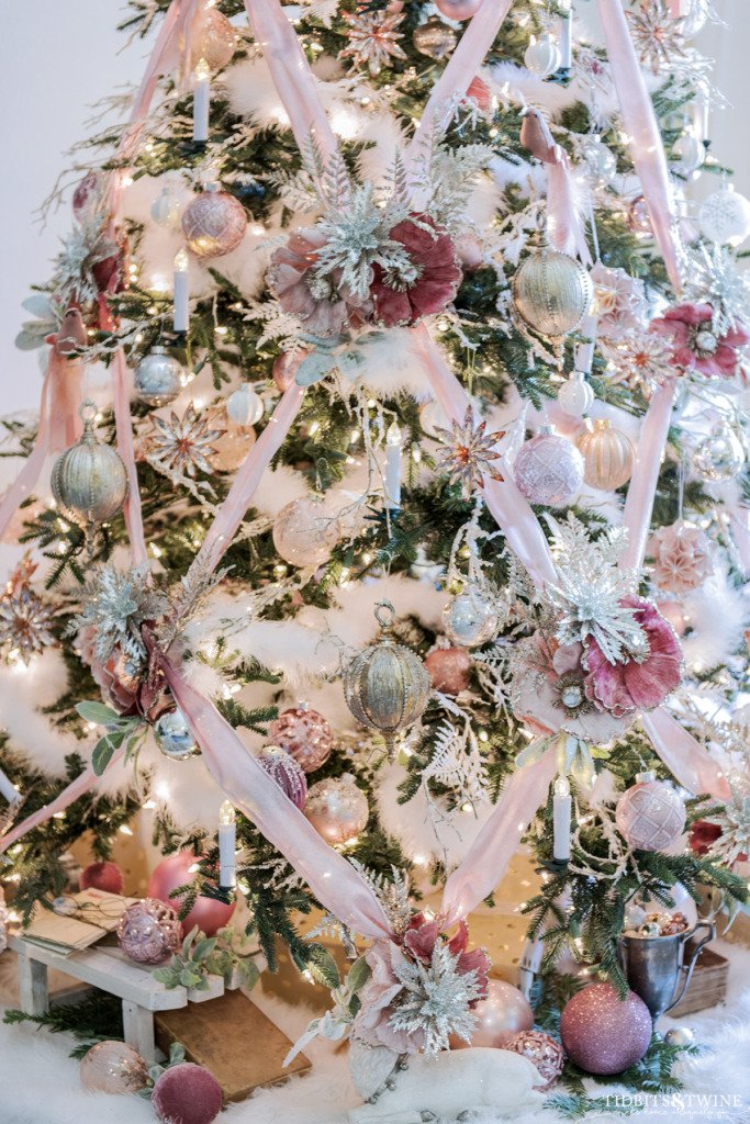 Crisscross ribbon on a pink Christmas tree with gold and silver accents