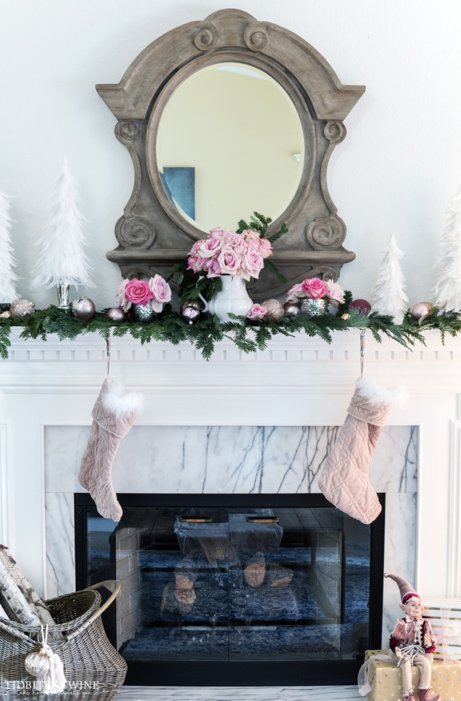 Pink and white Christmas fireplace mantel decor with mirror above