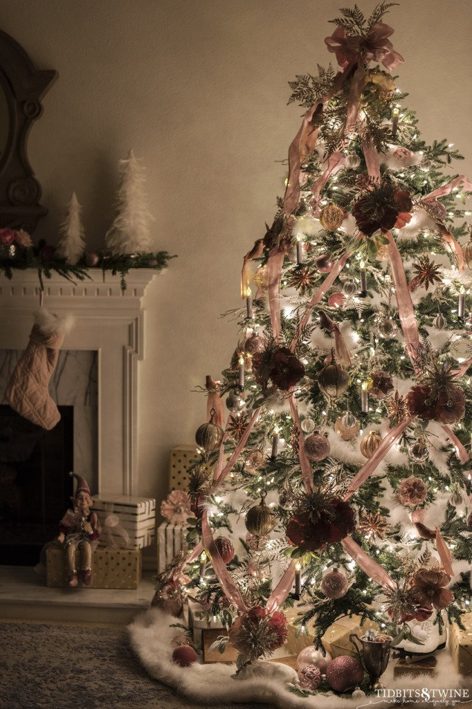 Pink and white decorated Christmas tree at night in French living room