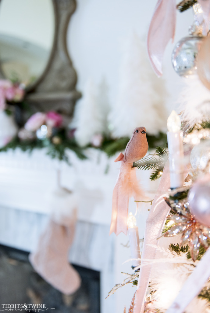 Pink bird and candle clip on Christmas tree with French fireplace mantel in the background