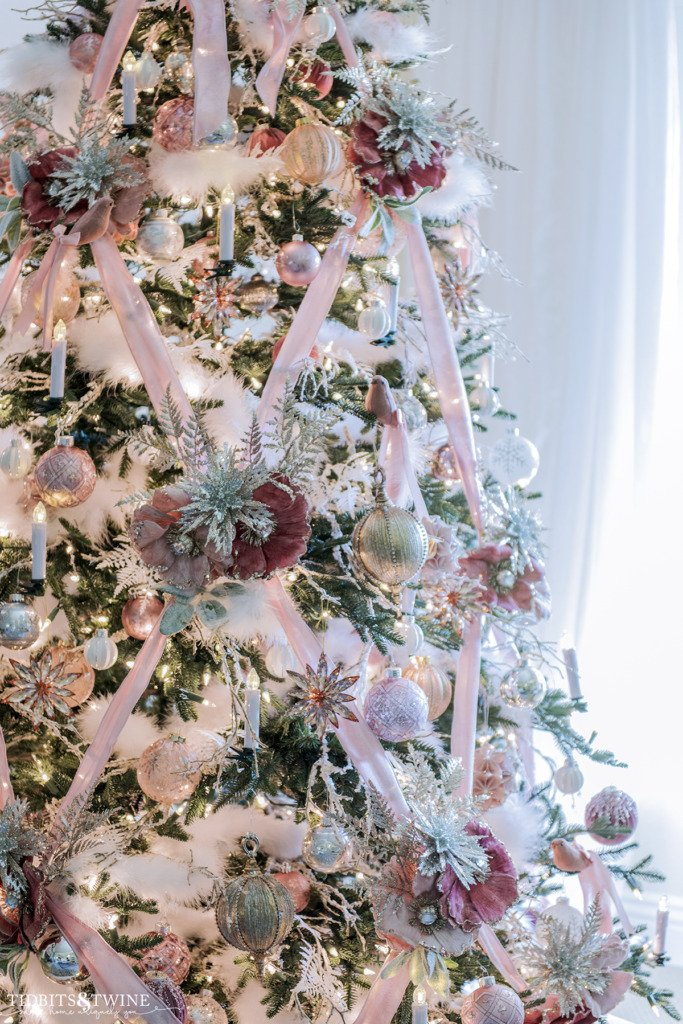 Pink Christmas tree with velvet ribbon and white accents.