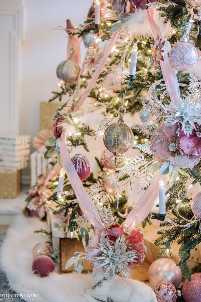 Lower half of Christmas tree decorated in pink with velvet ribbon