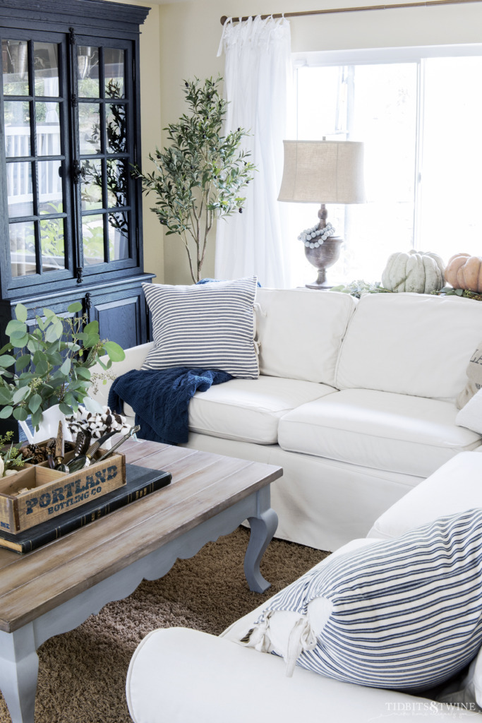White slipcovered sectional sofa with french blue coffee table and pumpkins