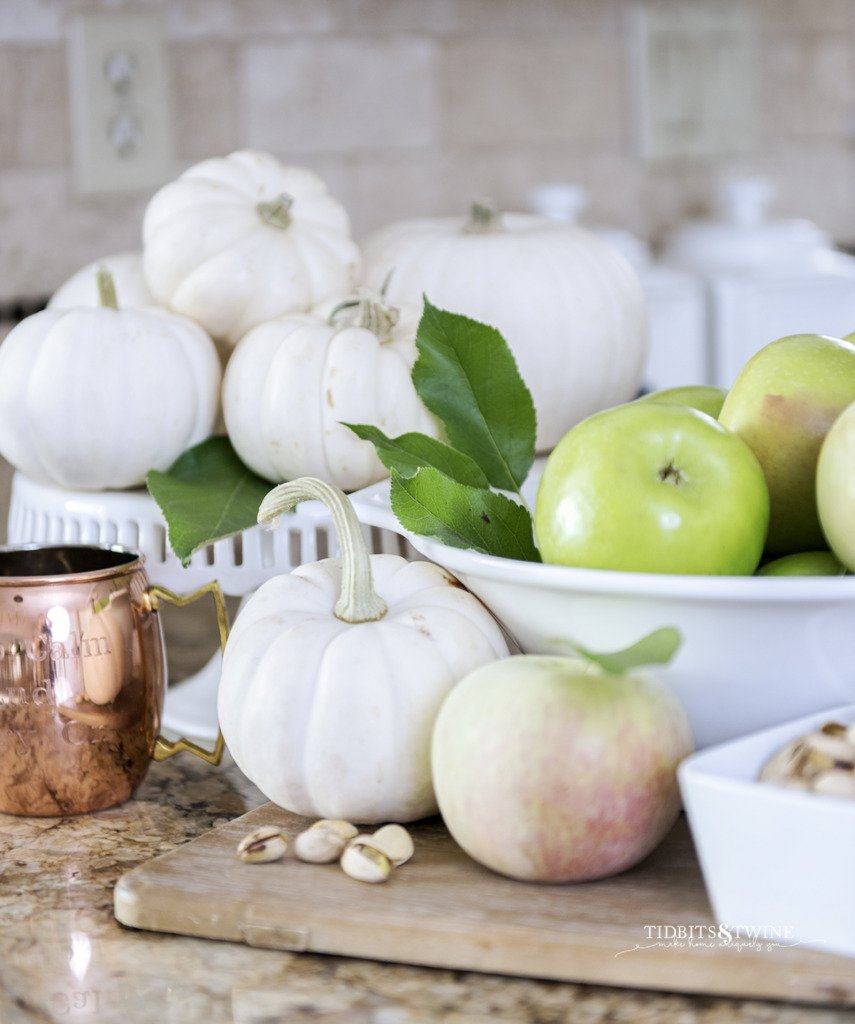 kitchen vignette with white bowl holding green apples and white pumpkins on a cake stand behind