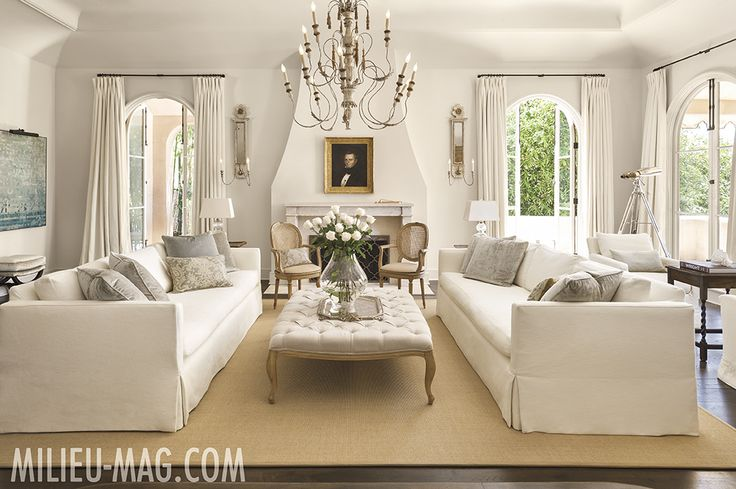 White living room with two white sofas and french tufted ottoman