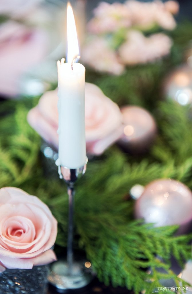 Closeup of taper candle with dripping wax and Christmas pink and green table in background