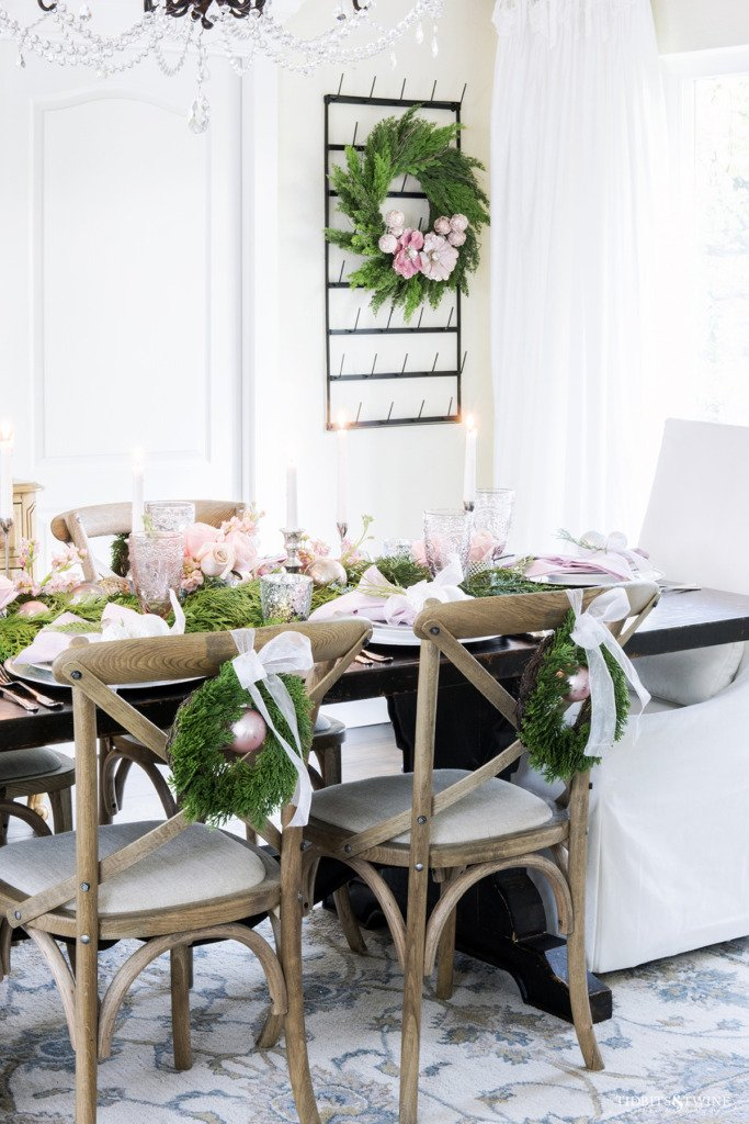 Dining room table decorated for Christmas with pink and white and cedar garland