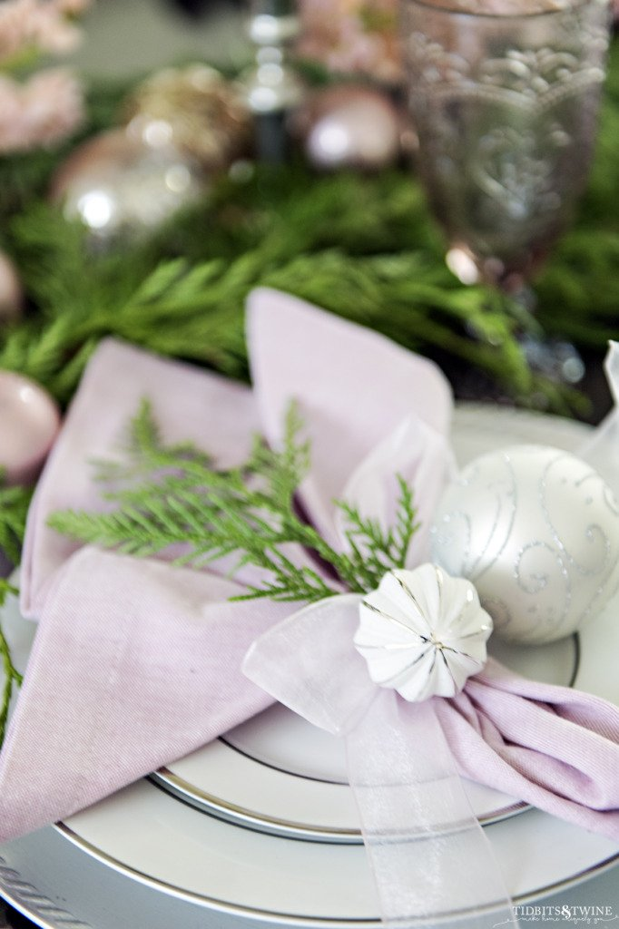 Closeup of christmas place setting tied with ribbon two white ornaments and cedar garland