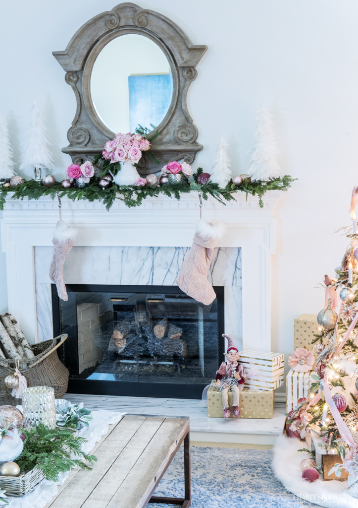 Living room fireplace decorated for Christmas in pinks and white