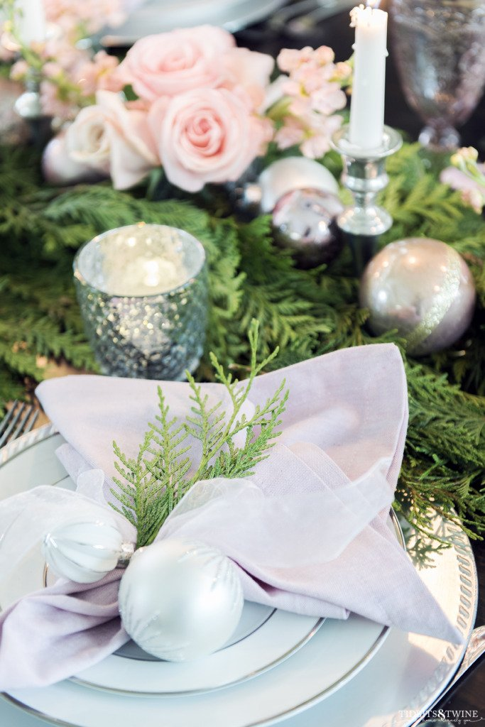 Christmas place setting with pink napkin tied with white ornaments and cedar sprig