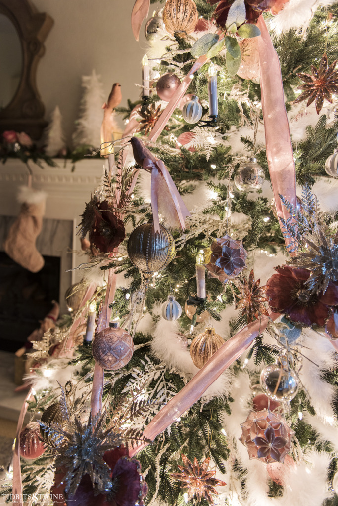 Closeup of pink and white decorated Christmas tree at night with fireplace in background