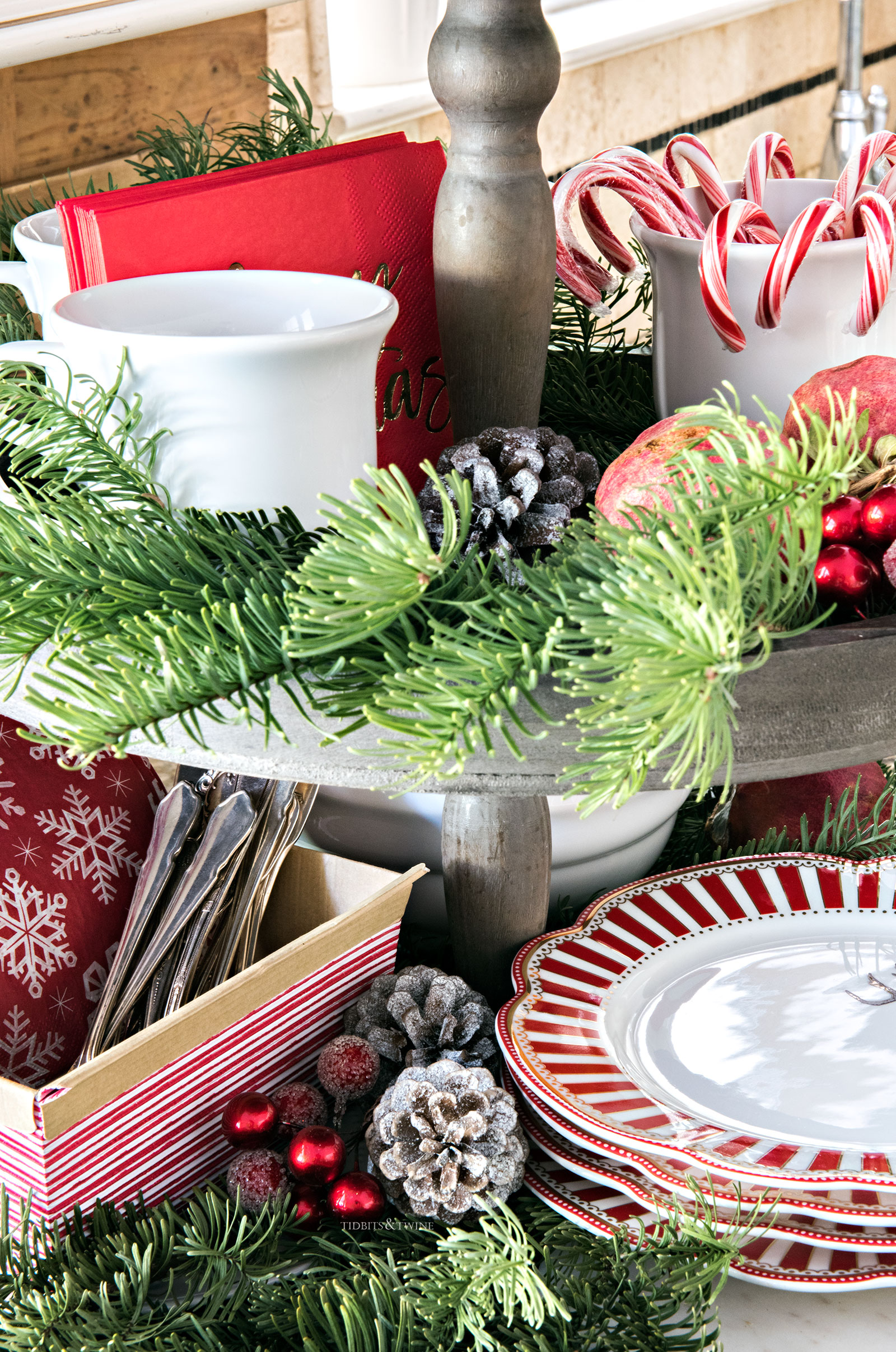 Tiered wooden tray with Christmas greens and berries white mugs with candy canes and hot chocolate