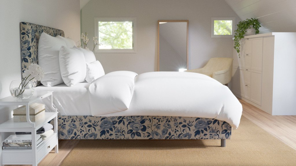 White bedroom with blue chintz upholstered bed with white bedding