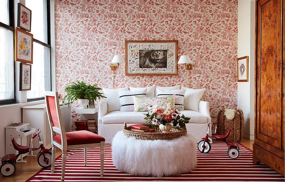 Red floral wallpaper on accent wall with red and white striped rug and white fuzzy ottoman