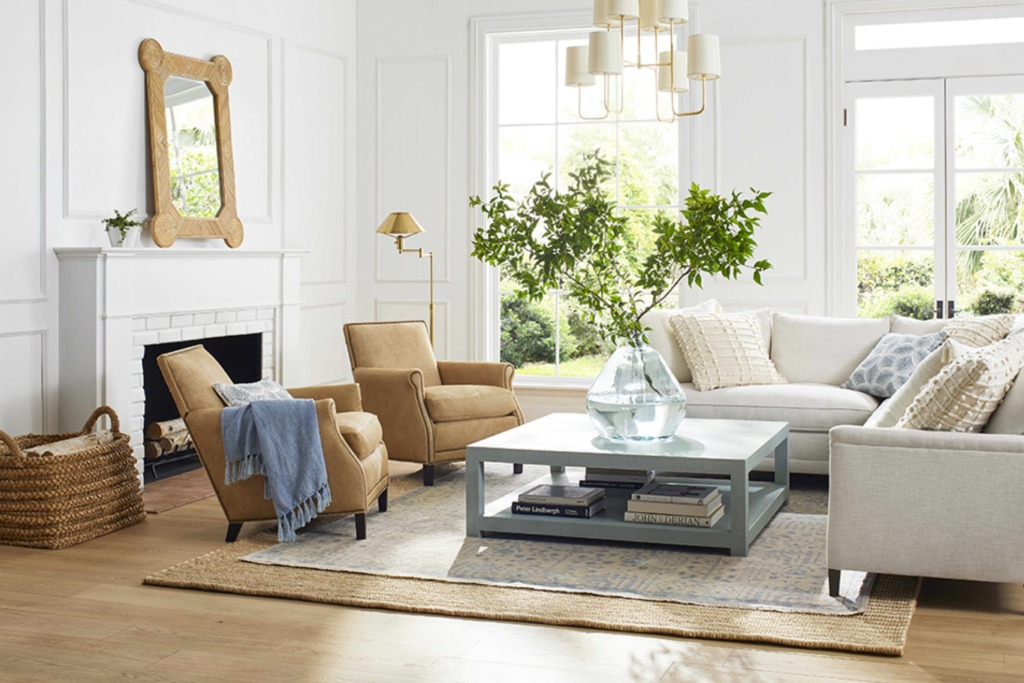 White living room with picture frame molding and white sectional with tan side chairs and oversized coffee table