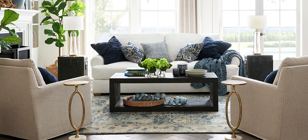 Living room with white sofa and blue throw pillows with potted fiddle leaf figs