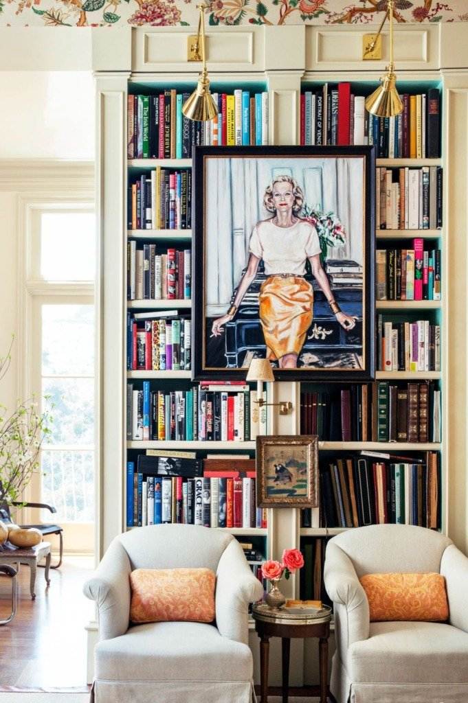 decorating cabinets with artwork hanging from frame of white bookcase