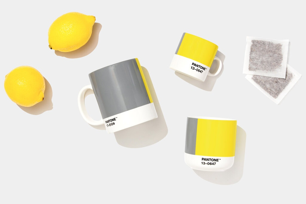 Pantone 2021 color of the year gray showing gray and yellow coffee mugs and lemons on a gray background
