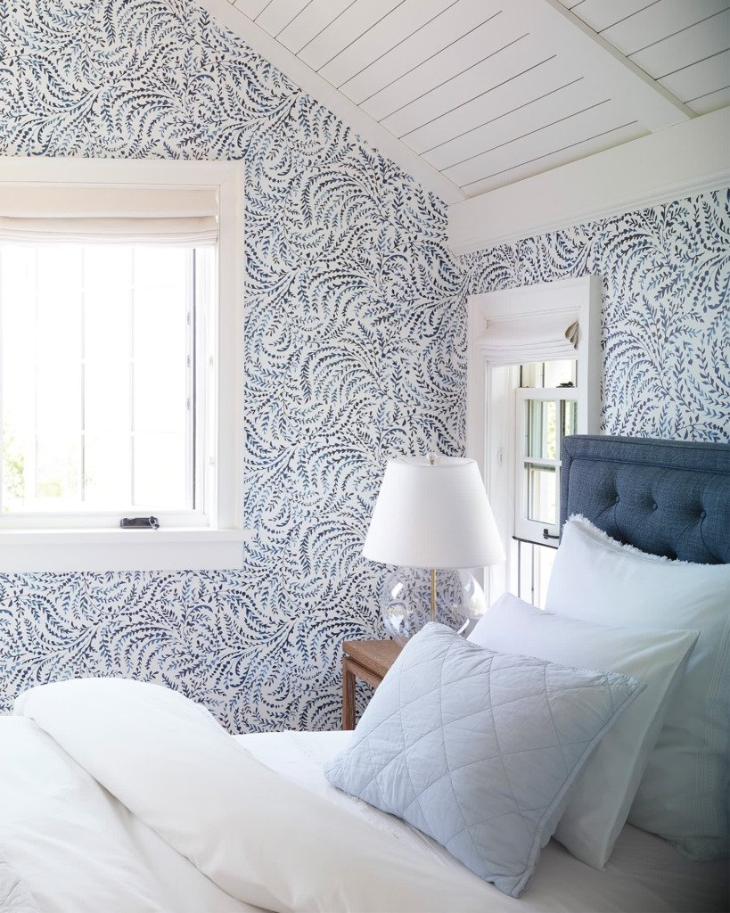 Bedroom with blue and white wallpaper white planked ceiling and blue tufted upholstered headboard