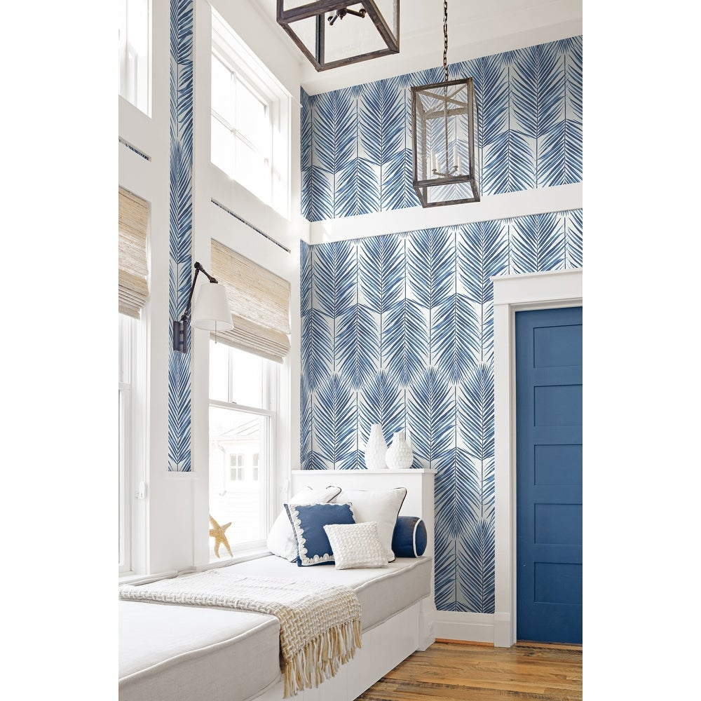 Tall entryway with blue leaf wallpaper and blue painted door and upholstered entry bench