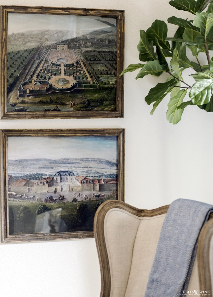 Large frame French chateau artwork hanging on wall behind wingback chair