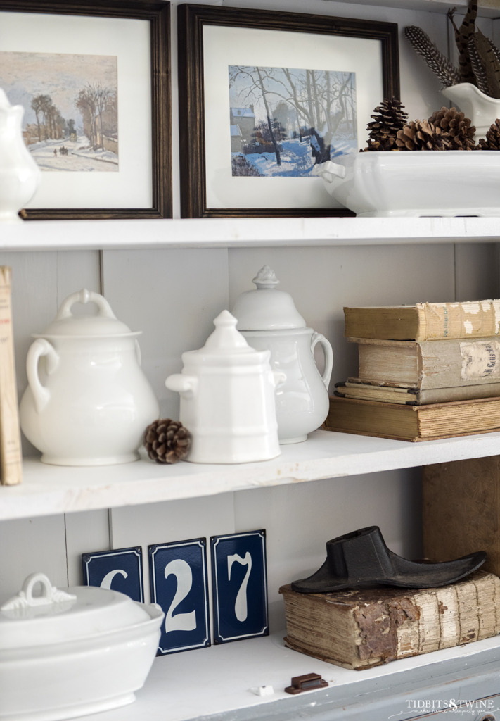 Closeup of white ironstone and winter artwork on white bookshelves