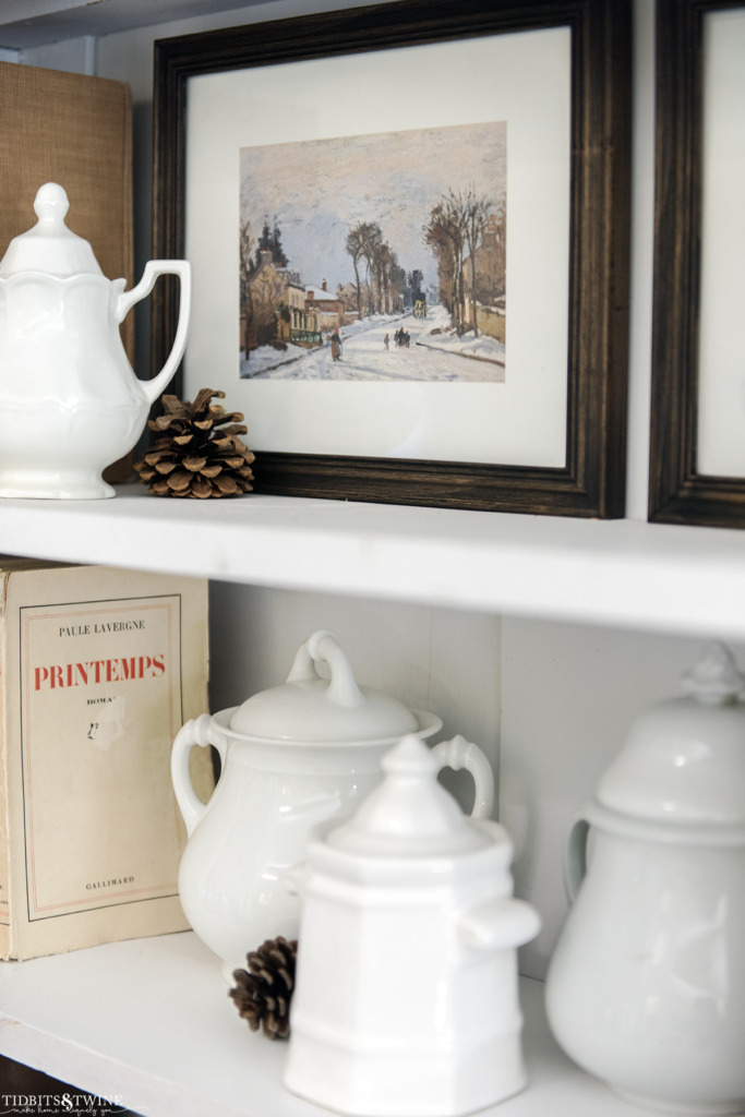 Framed winter scene artwork and books style on French bookcase
