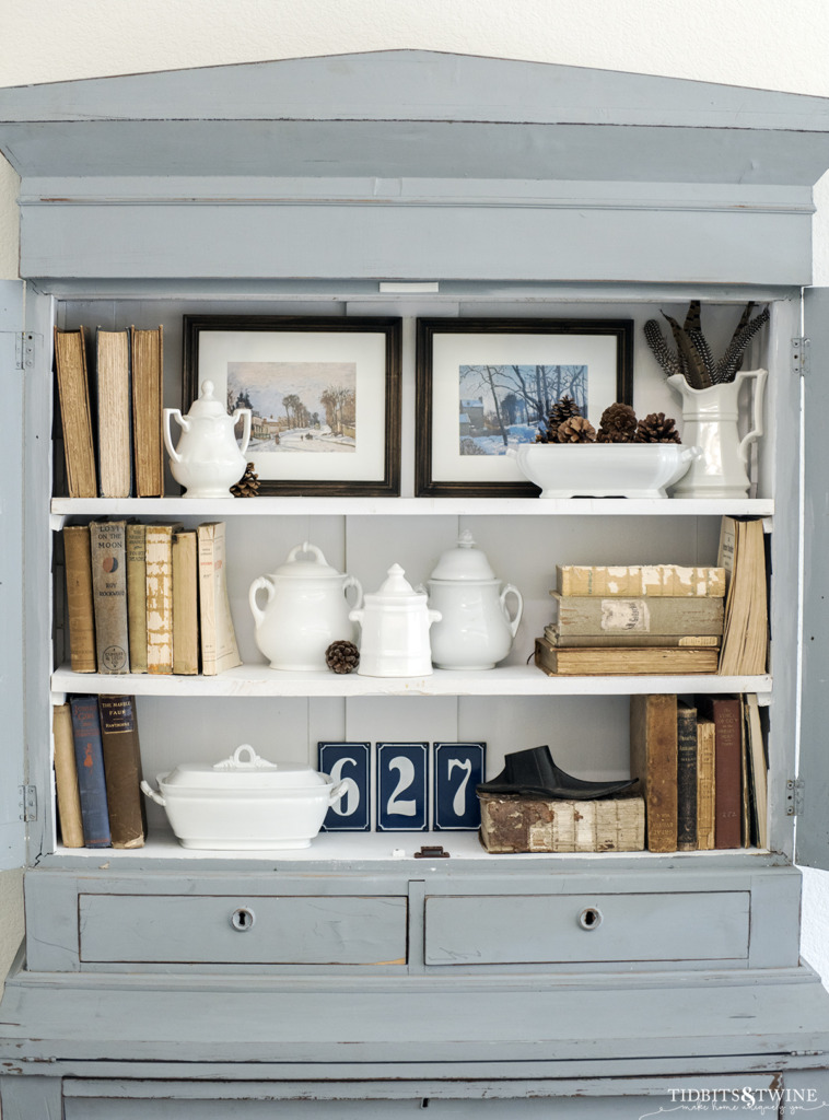 Blue French hutch styled with white ironstone antique books and free winter artwork