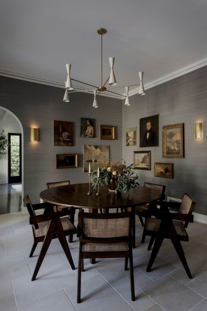 Gray grasscloth dining room with dark wood round table and modern light fixture and antique oil paintings on wall