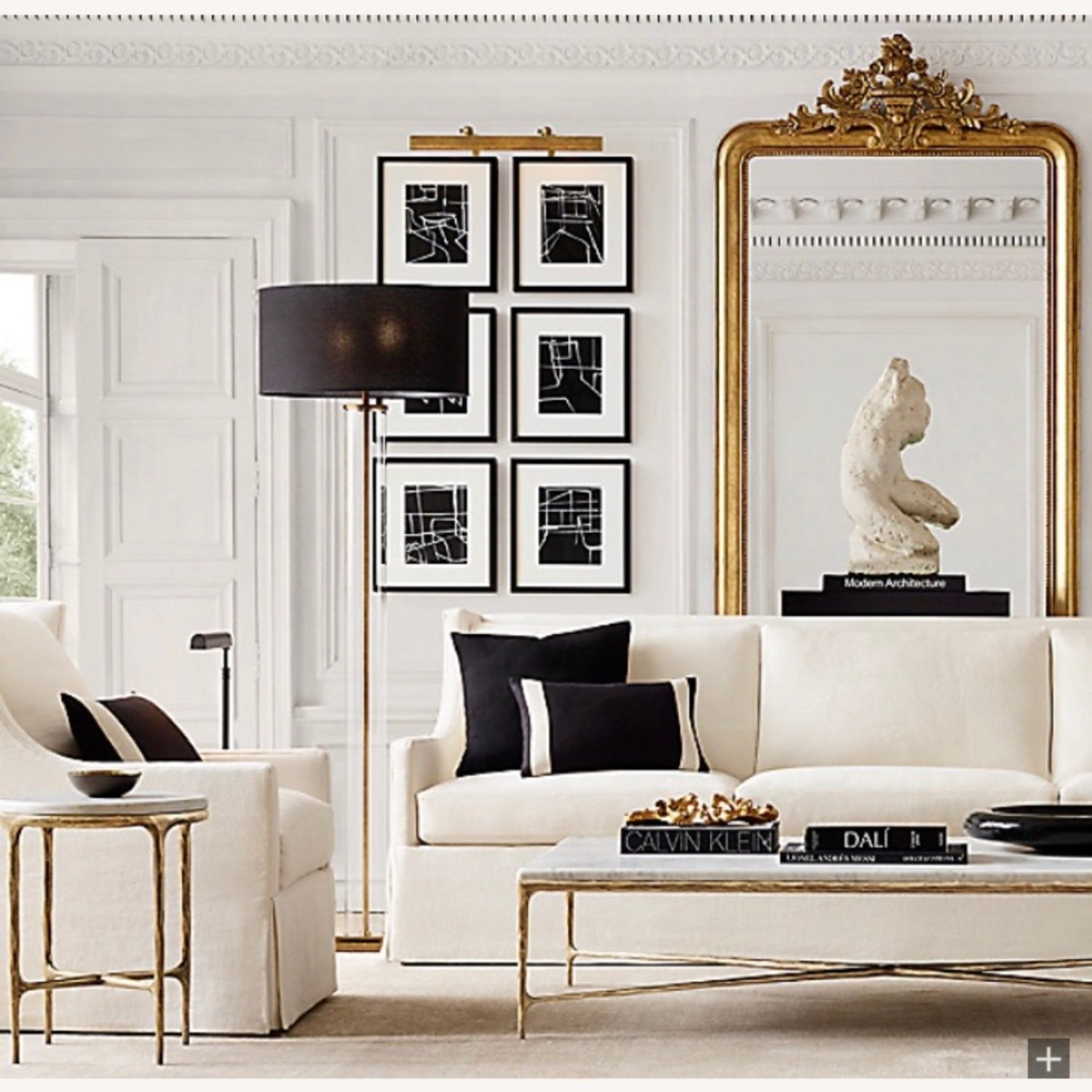 White modern living room with black and gold accents and oversized ornate gold French mirror