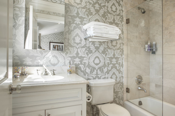 Small bathroom with beige wallpaper and white single sink