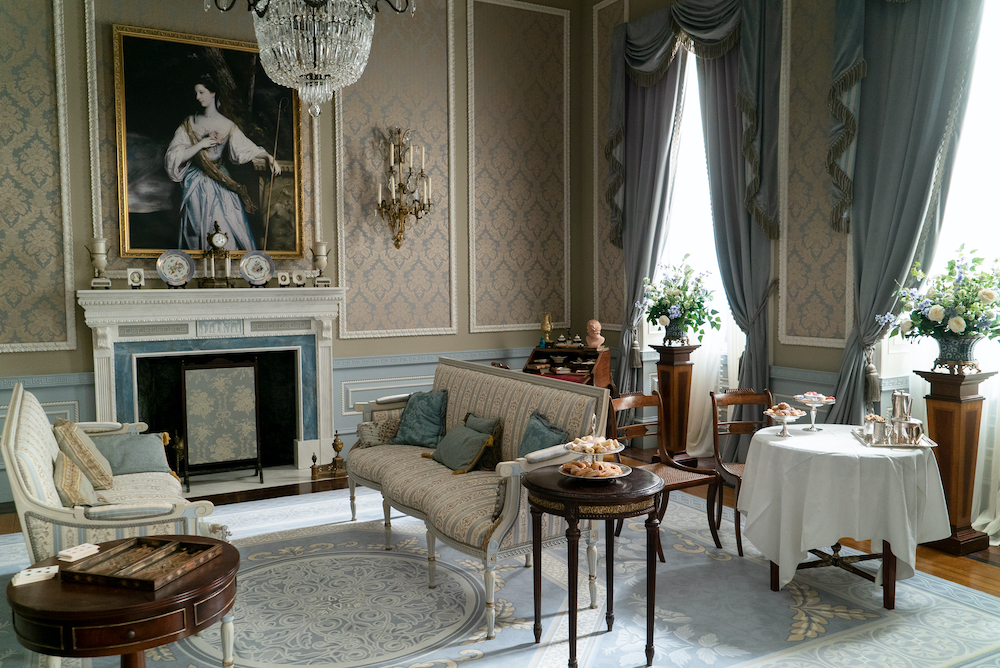 Netflix Bridgerton living room with blue and beige wallpaper and Regency furnishings