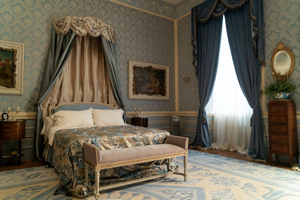 Netflix Bridgerton Regency style bedroom with blue wallpaper and bed with crown above