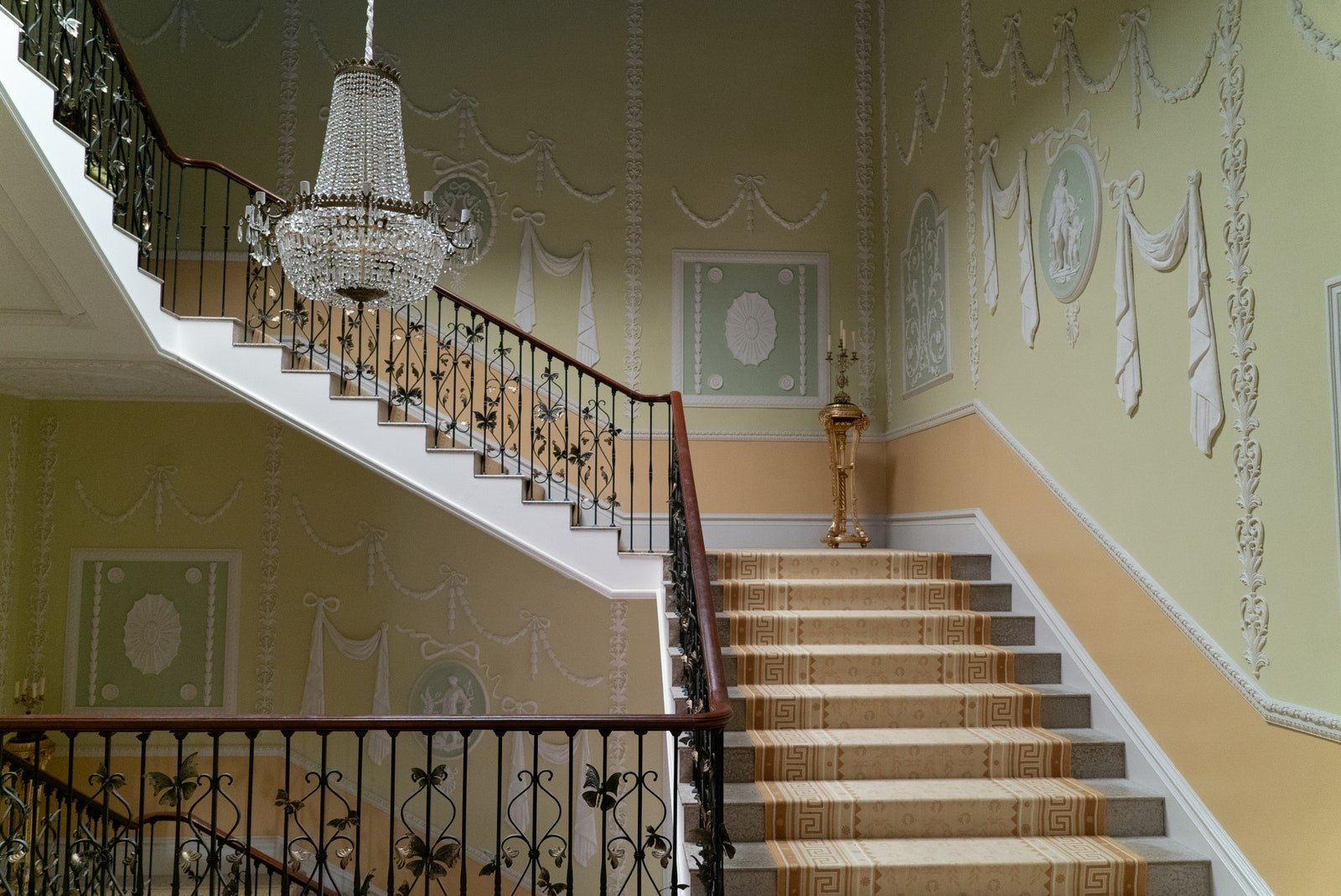 Netflix Bridgerton stairway with green walls and millwork and butterfly railing