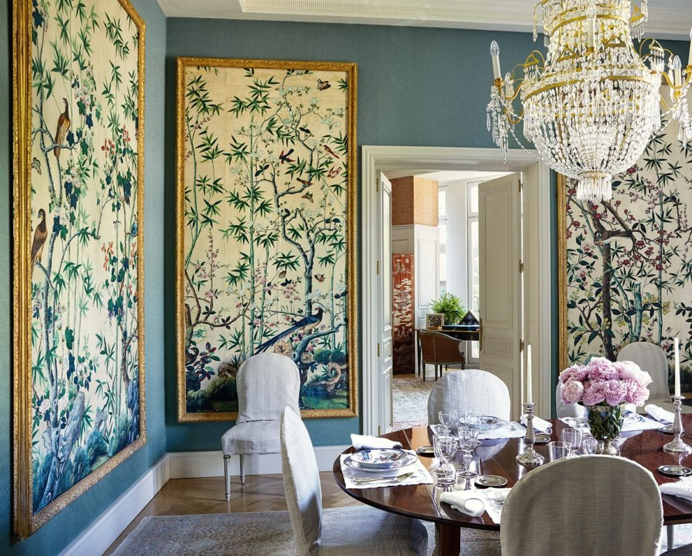 Turquoise dining room with chinoiserie panels framed in gold with dark wood table and linen chairs