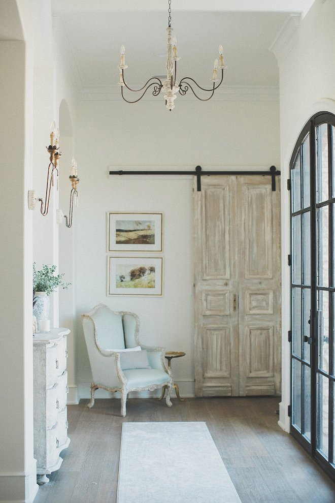 French entryway with cabinet flanked by French sconces and a light blue chair