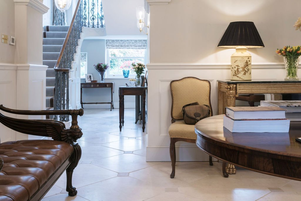white tiled entryway with regency dark wood furnishings and light colored walls