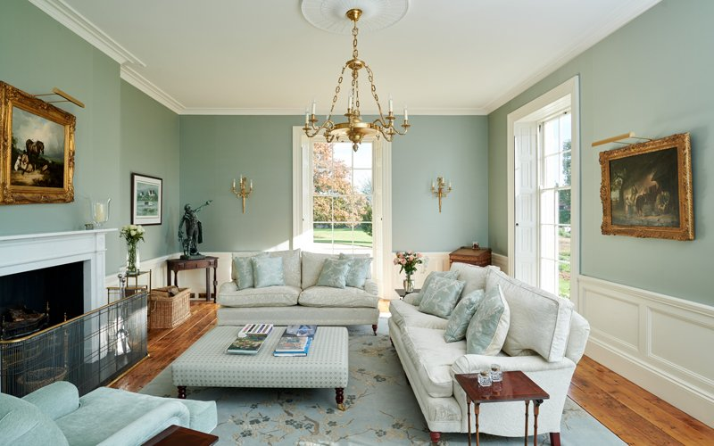 Georgian living room with light blue walls and rug white sofas and gold accents