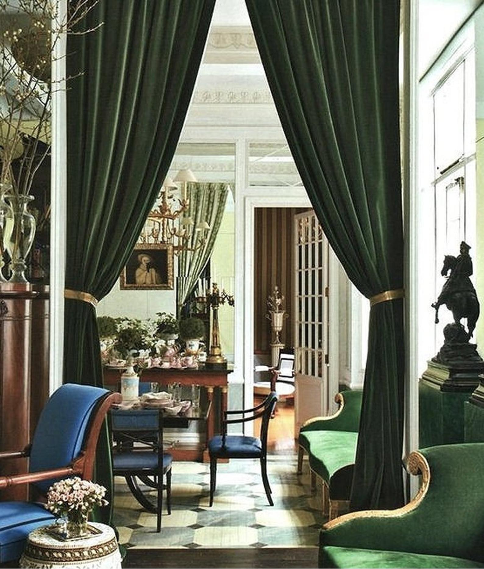 Green velvet curtains flanking entrains to a regency style dining room