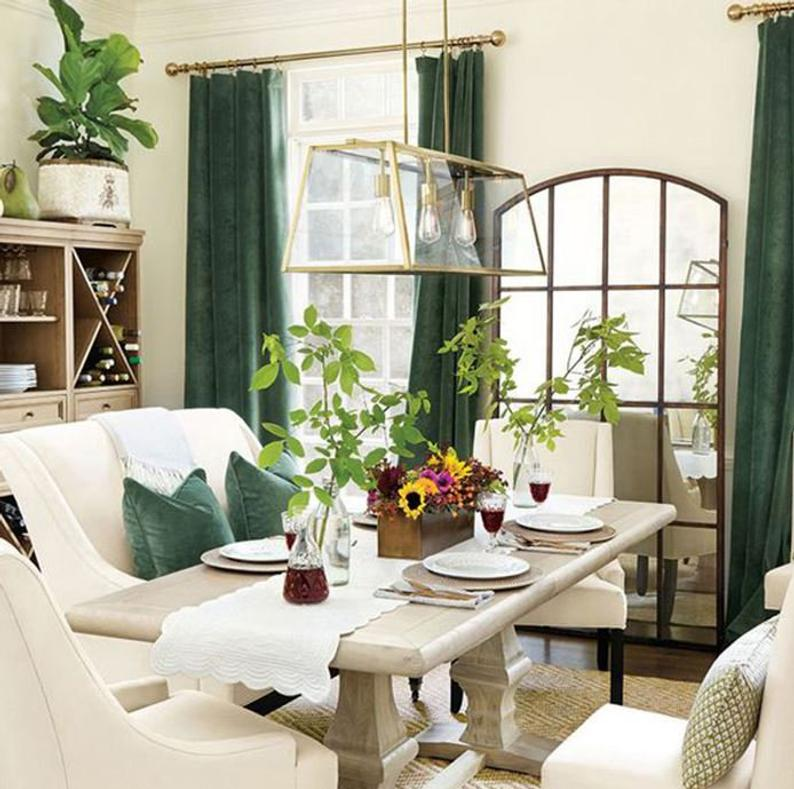 trestle dining table with white bench seat and green velvet accents
