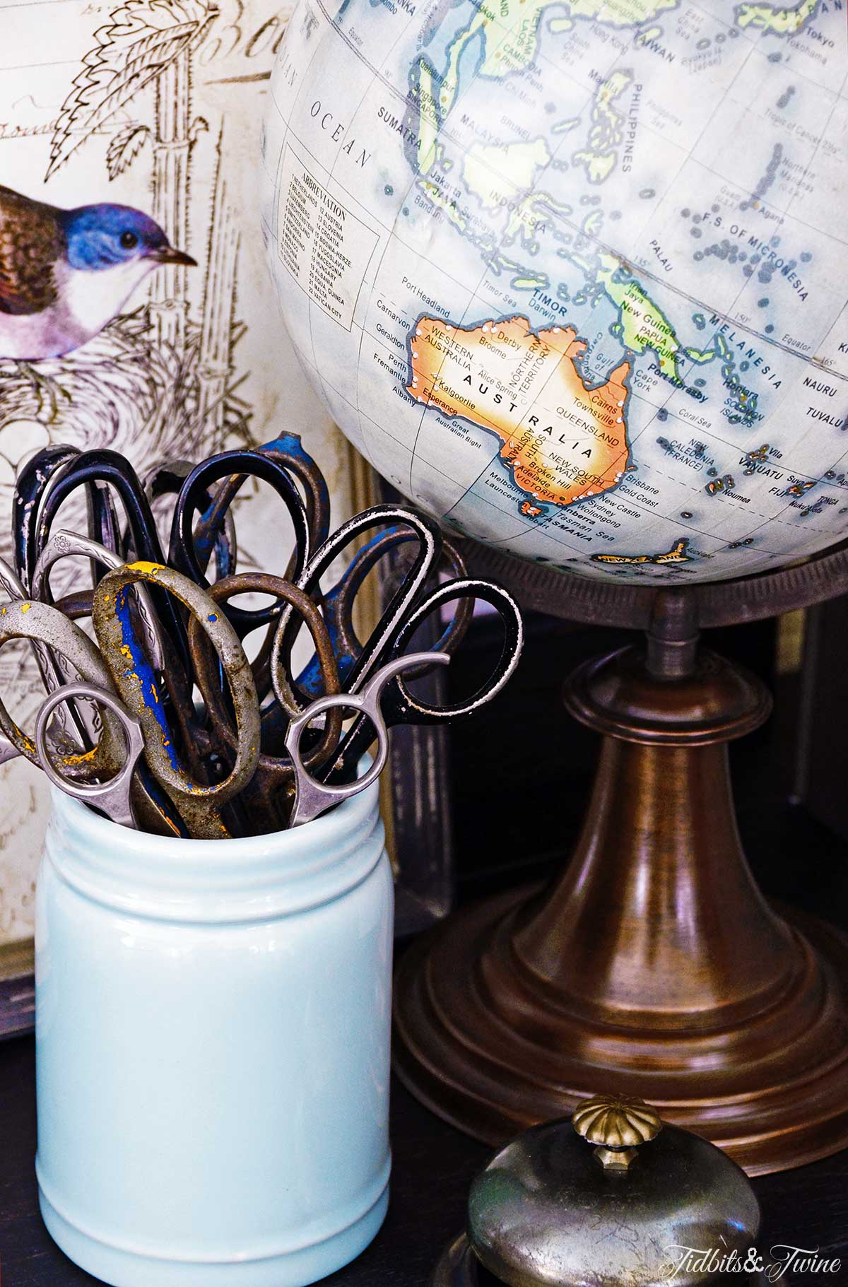 Closeup of antique scissors in a blue mason jar next to a globe