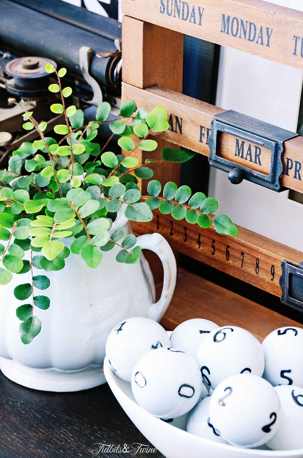 A wooden desk calendar next to antique white ironstone holding a button fern and glass numbered balls