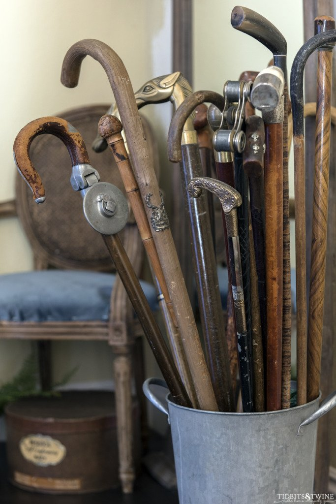 bucket full of antique canes in an entryway with blue chair in background