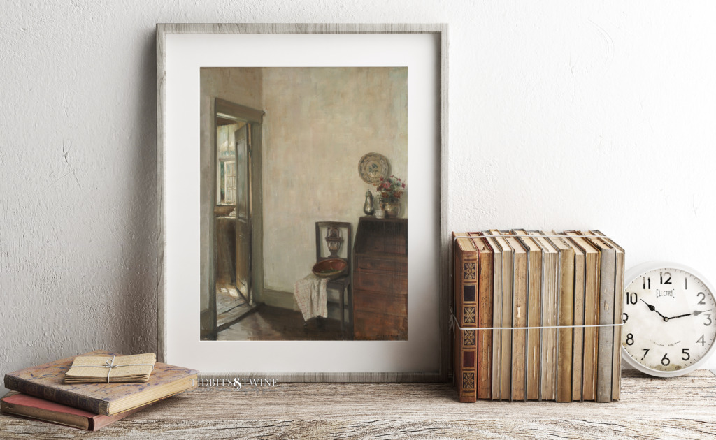 Framed artwork of Carl Holsoe on shelf with antique books and old alarm clock