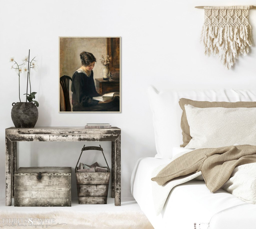 Framed artwork of Carl Holsoe above nighstand with orchid and white bedding