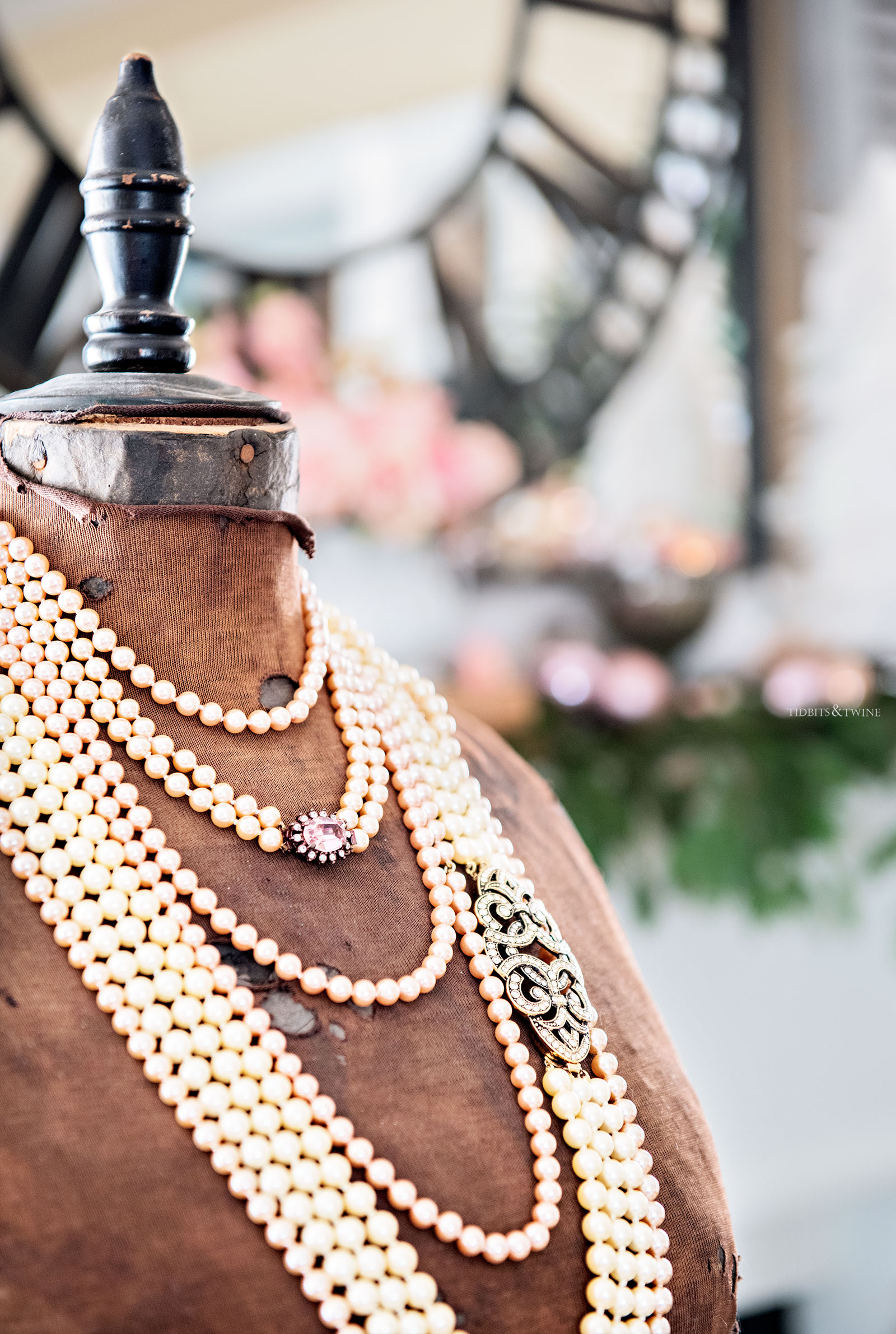 brown antique dress form with multiple strands of white pearls around neck and pink and green christmas decor in background