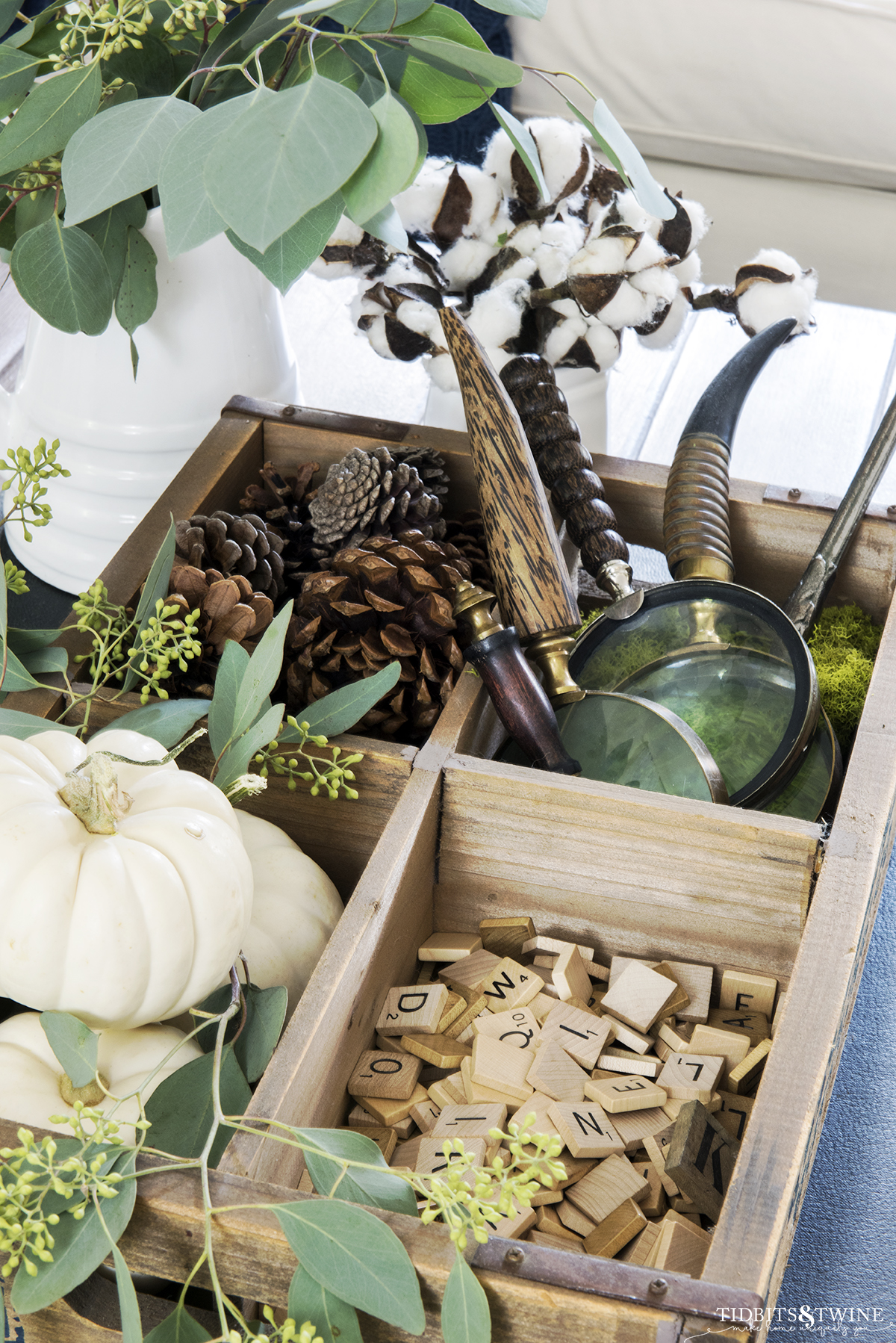 Wooden crate holding white pumpkins scrabble tiles and magnifying glasses