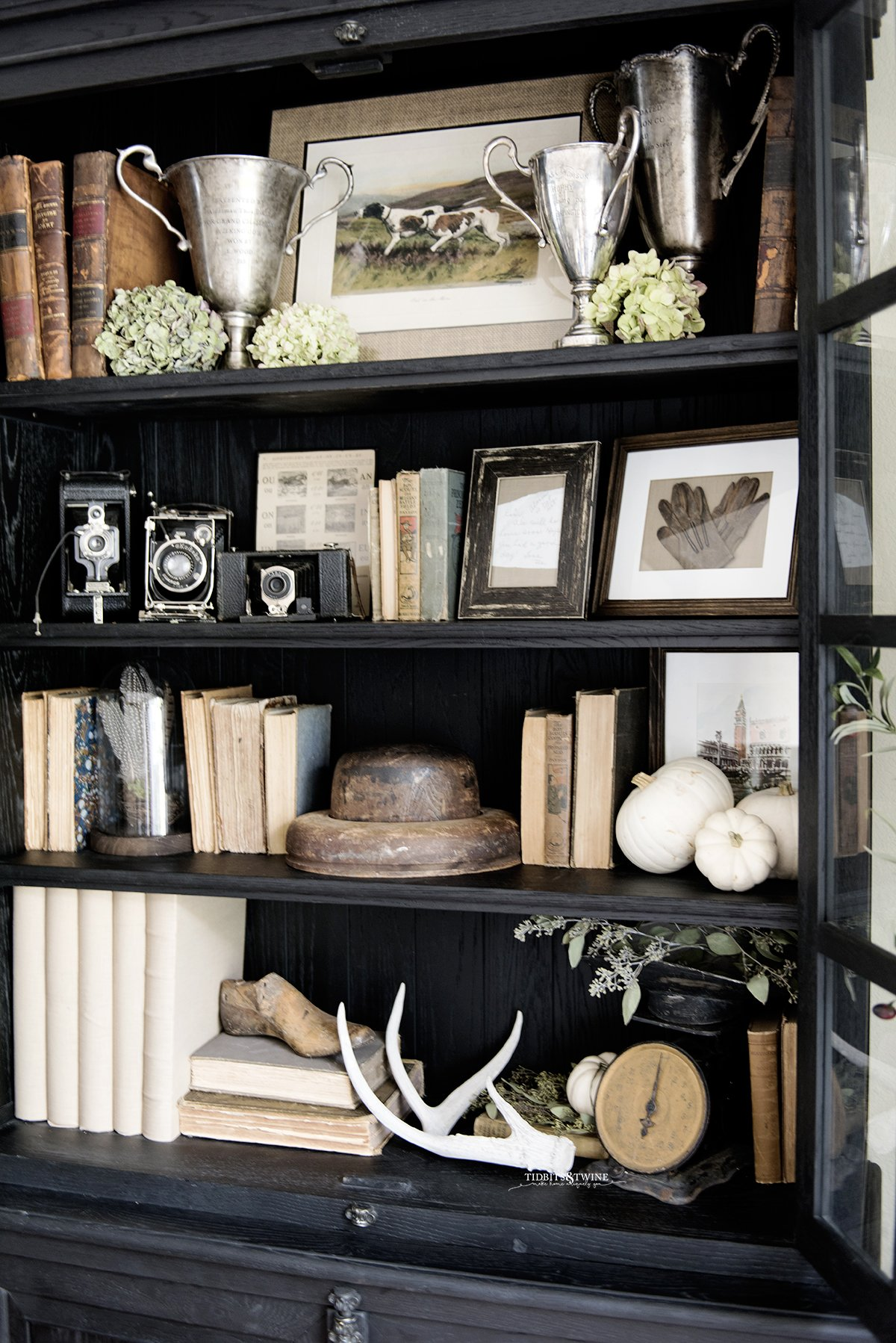 black french cabinet decorated for fall with antique books trophies and dried hydrangea