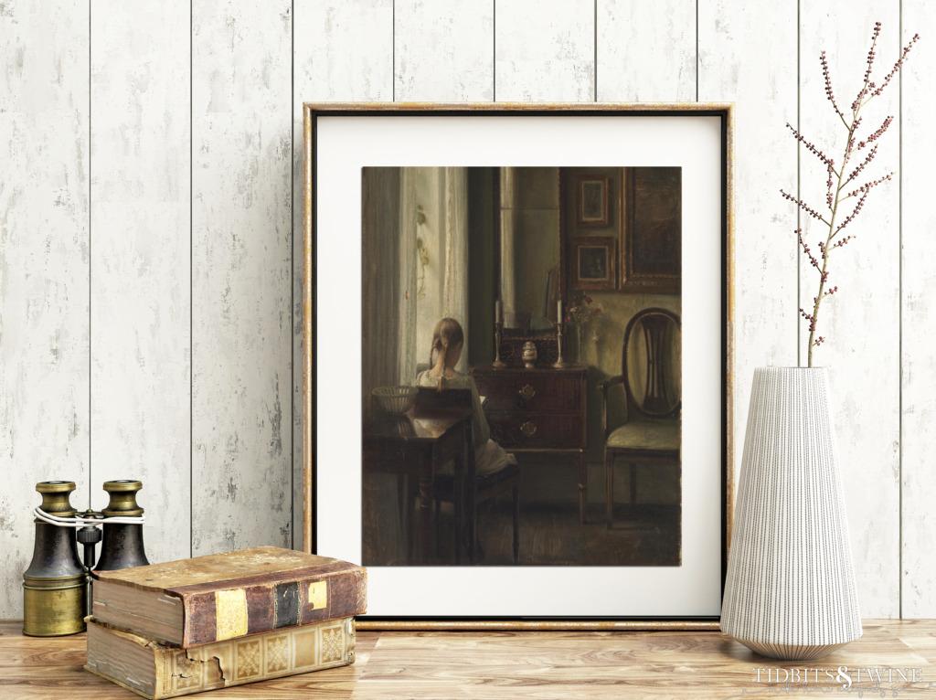 Gold framed Carl Holsoe art of back of girl sitting reading book